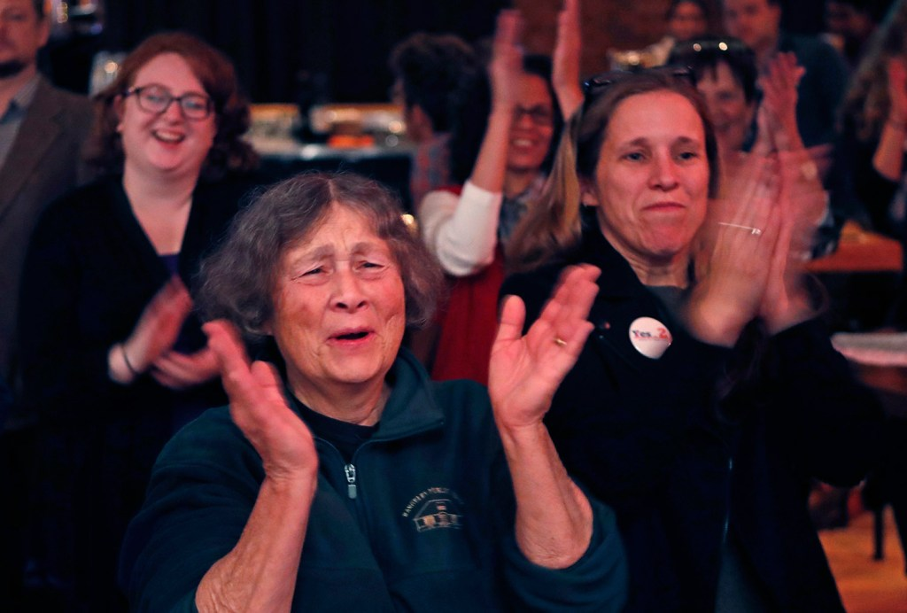 Chris Hastedt, left, and Robyn Merrill cheer during an announcement while awaiting results at the Mainers for Health Care election night party on Tuesday in Portland. Voters decided to join 31 other states and expand Medicaid under former President Obama's Affordable Care Act.