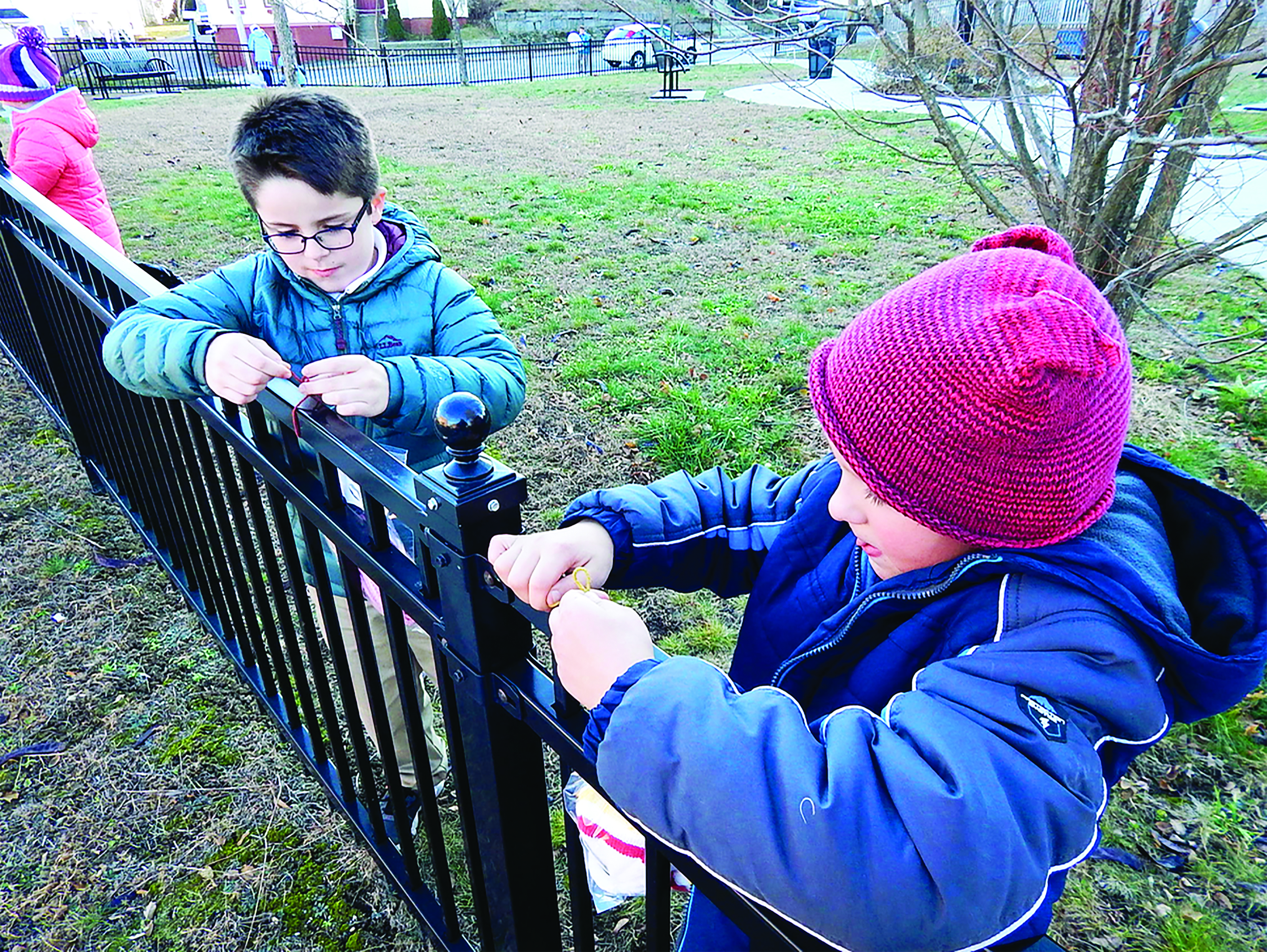 St. James School fourth-graders Aiden Leighton, left, and Zackary Namiotka hang bags containing hats, gloves, scarves and other winter wear items on the fence surrounding the city park at the corner of South and Green streets in Biddeford on Tuesday afternoon. More than a dozen students from the school left the items for anyone in need of them in an 'act of service' on 'Giving Tuesday.