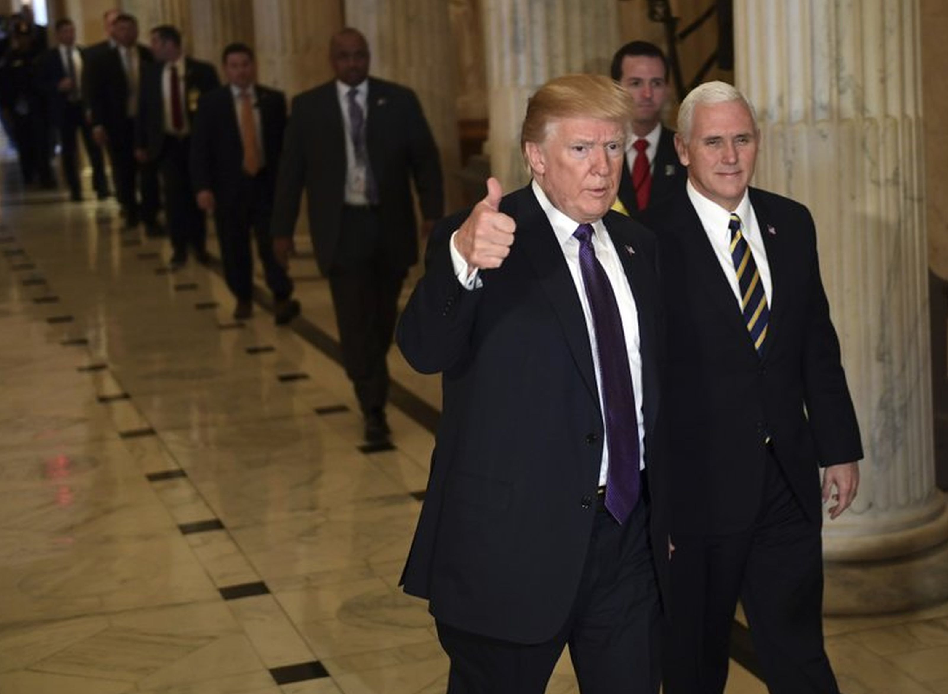 President Donald Trump gives a thumbs up as he walks with Vice President Mike Pence as he departs Capitol Hill in Washington, Thursday, Nov. 16, 2017. Trump urged House Republicans Thursday to approve a near $1.5 trillion tax overhaul as the party prepared to drive the measure through the House. Across the Capitol, Democrats pointed to new numbers showing the Senate version of the plan would boost taxes on lower and middle class Americans. AP NEWSWIRE/Susan Walsh