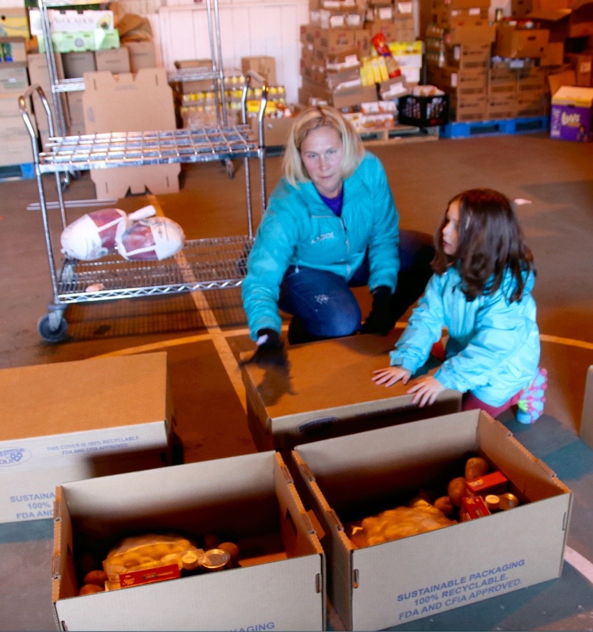 Deb Carson of Gray and Acadia Regan of Dayton were among the volunteers helping pack Thanksgiving food boxes at York County Shelter Programs in Alfred on Tuesday.  TAMMY WELLS/Journal Tribune