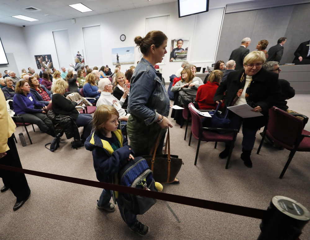 Residents filter into a hearing room to attend the Douglas County School Board meeting, Monday, Dec. 4, 2017, in Castle Rock, Colo. A new anti-voucher majority on the board was set to eliminate a program enacted by an earlier conservative-dominated board to help public school students attend secular and religious schools with taxpayer-funded vouchers. (AP Photo/David Zalubowski)