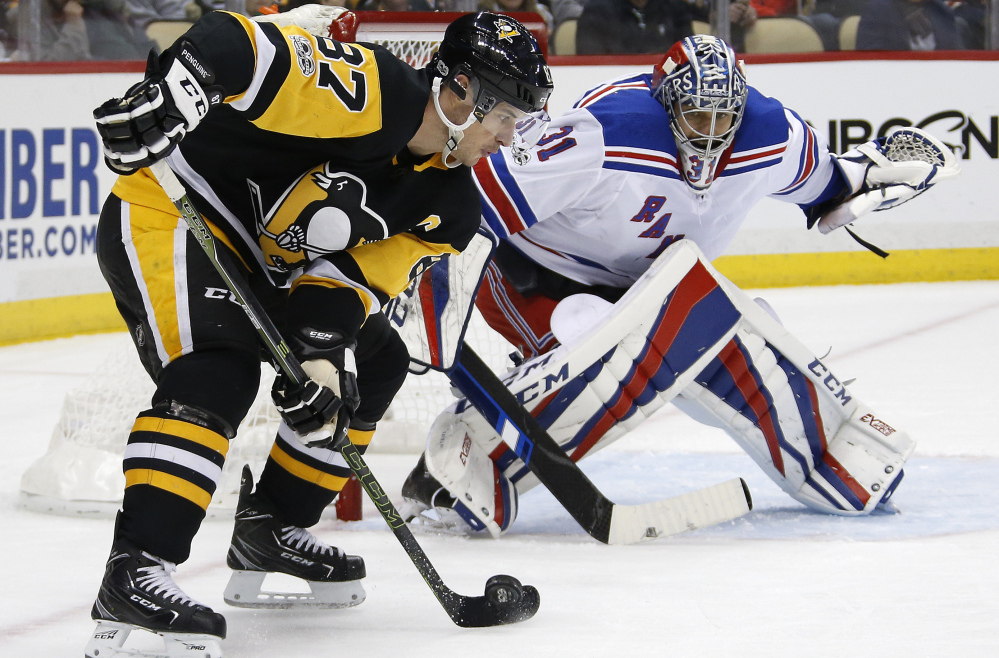 Pittsburgh's Sidney Crosby works to get off a shot in front of Rangers goalie Ondrej Pavelec during New York's 4-3 win Tuesday. Crosby was held off the scoresheet, ending a run of five straight multipoint games.