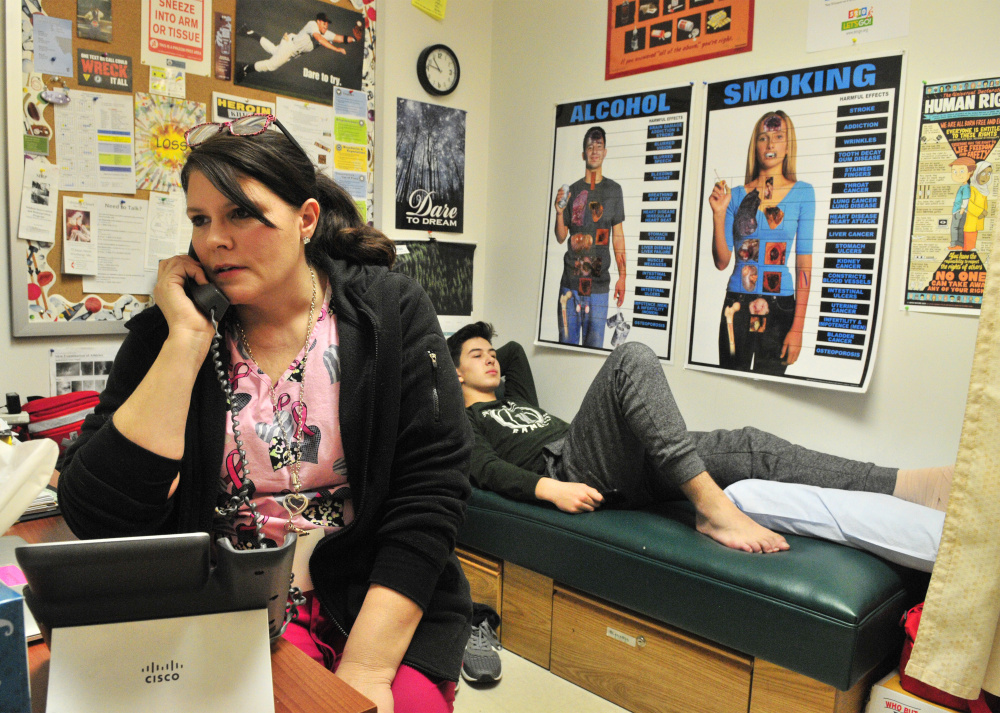 Winthrop school nurse Rachel Miville, left, calls the parents of Noah Dunn, right, to come and pick him up after she wrapped up his ankle in her office Thursday at the high school in Winthrop.