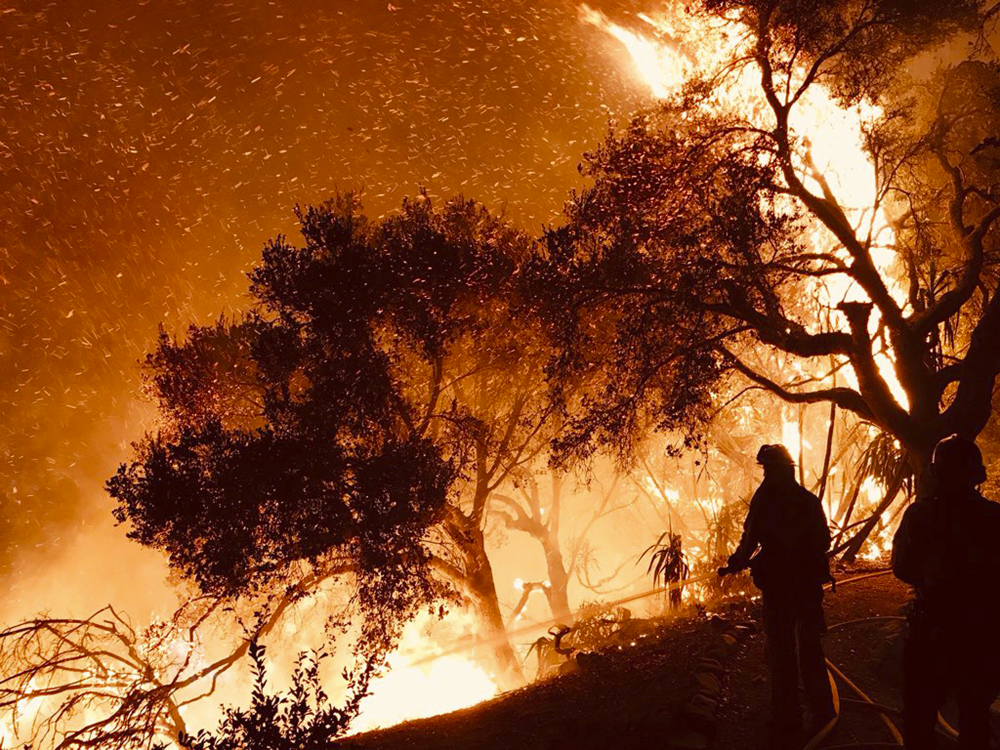 In this photo released Sunday by the Santa Barbara County Fire Department, firefighters knock down flames as they advance on homes atop Shepherd Mesa Road in Carpinteria, California. A flare-up on the western edge of Southern California's largest and most destructive wildfire sent residents fleeing.