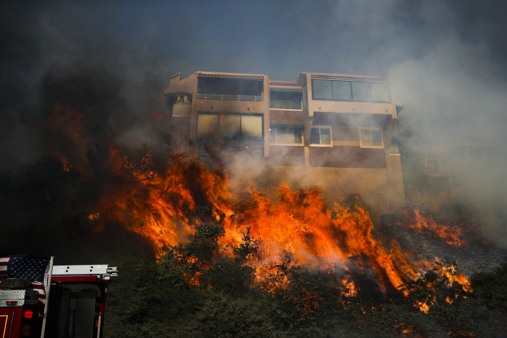 """A wildfire threatens a home in Ventura, Calif. Democrats have assailed Republicans for omitting California's wildfire victims from the House bill's tax advantages for disaster victims. """"If they call out one kind of devastation over another, that stinks,"""" Californian Larry Keyser said."""
