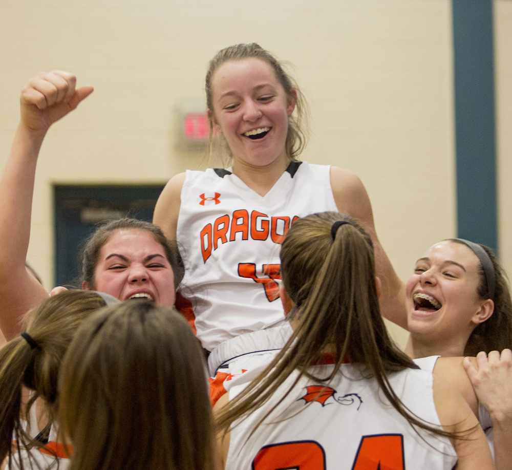 Junior point guard Marley Groat gets the hero's welcome from her teammates after hitting the winning shot, giving her 17 points for the game and lifting the Dragons to a 6-0 record.