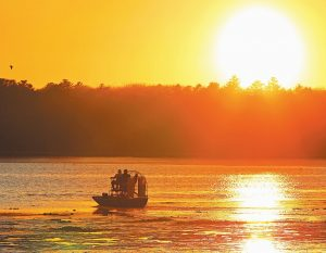 CLAMMERS MAKE THEIR WAY across Maquoit Bay in Brunswick in an airboat at sunset in September.