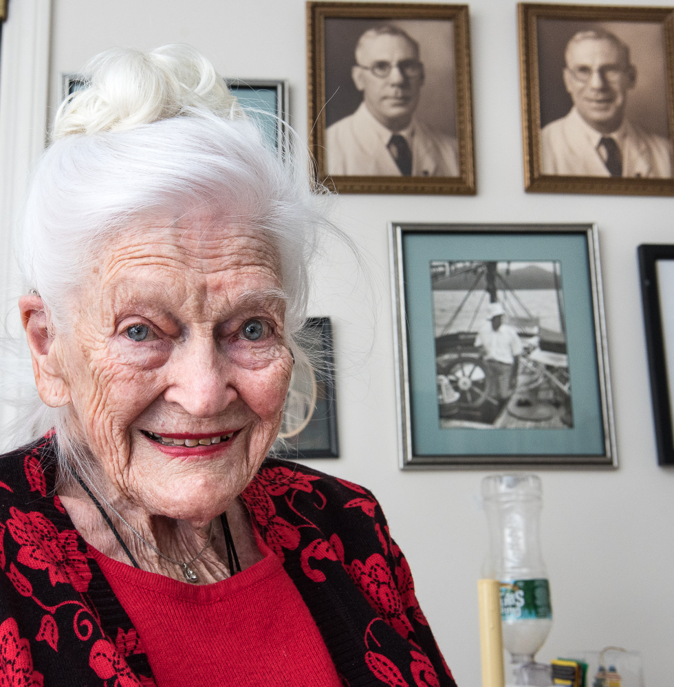 Hope Weston relaxes in her apartment Wednesday at Schooner Estates in Auburn. Behind her are photographs of her father when they lived in the Philippines before World War II, when the country was a U.S. possession.