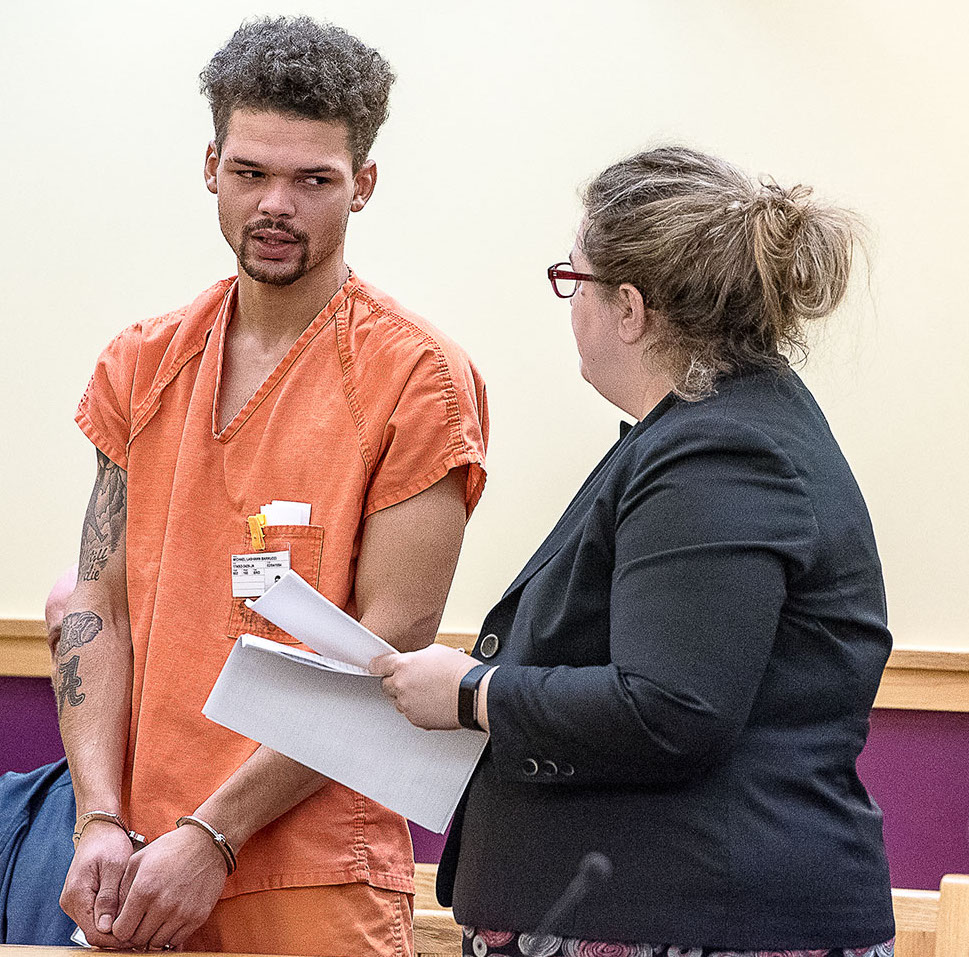 Micael Barrucci talks with his lawyer, Heidi Pushard, on Friday during his initial court appearance in Lewiston on a charge of elevated aggravated assault.