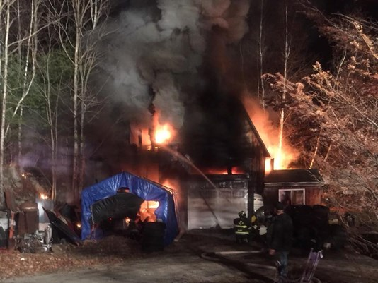 A garage fire in Casco destroyed two cars and blocked traffic on Route 11 for nearly 4 hours.
