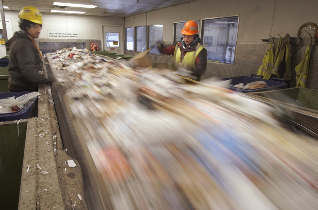 Hector Reinos, left, and Arturo Santos remove plastics from a conveyor of paper to be recycled at ecomaine in Portland last week. China instituted a ban on imports of 24 kinds of recyclable materials starting Jan. 1, shrinking a major market for recyclables from the U.S.