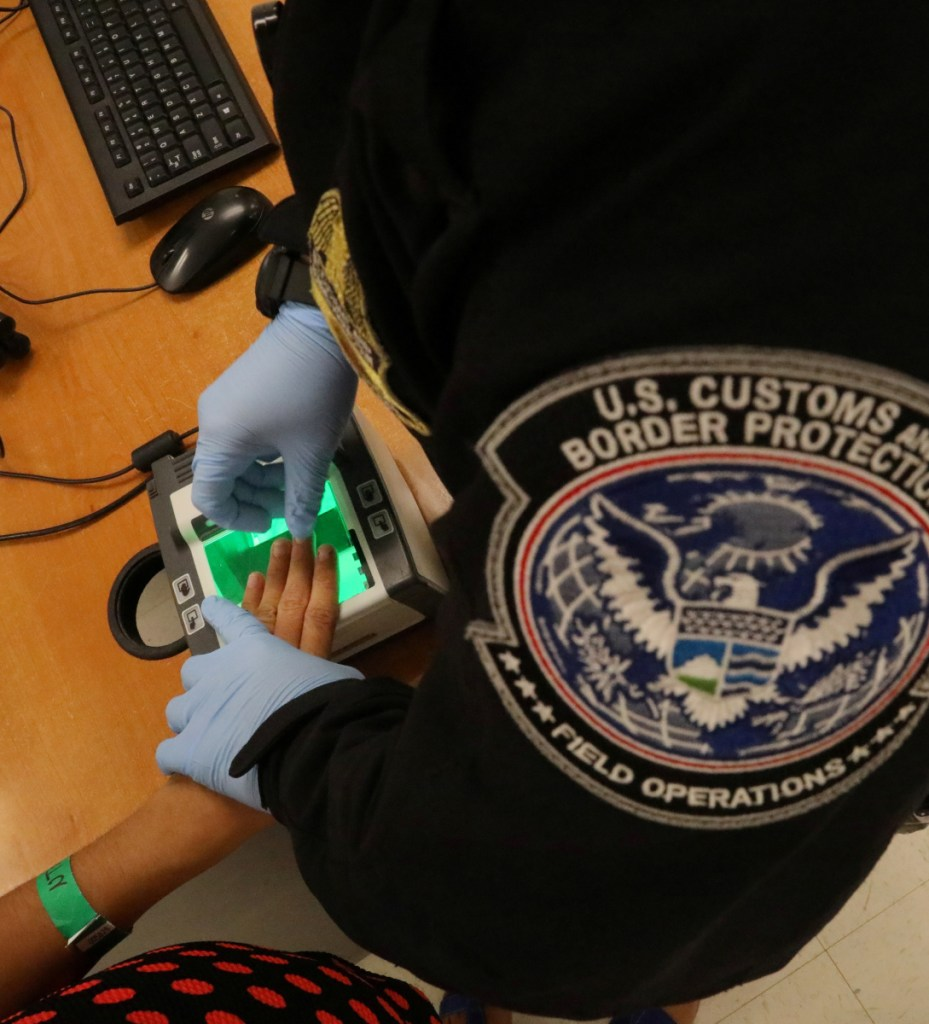 A woman who is seeking asylum has her fingerprints taken by a U.S. Customs and Border Protection officer in McAllen, Texas, last May. A law student in Portland says all is not dark in immigrants' fight.