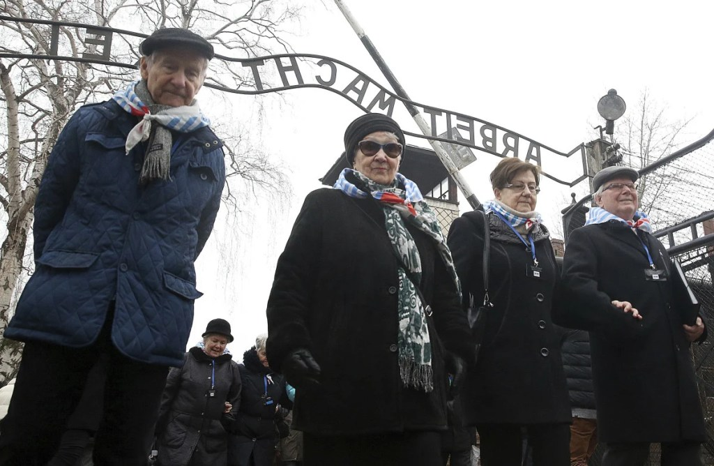 "Survivors and guests walk past the ""Arbeit Macht Frei"" gate at the former Nazi German concentration camp on International Holocaust Remembrance Day in Oswiecim, Poland, on Saturday. It is the 73rd anniversary of the liberation of Auschwitz-Birkenau by the Soviet army."
