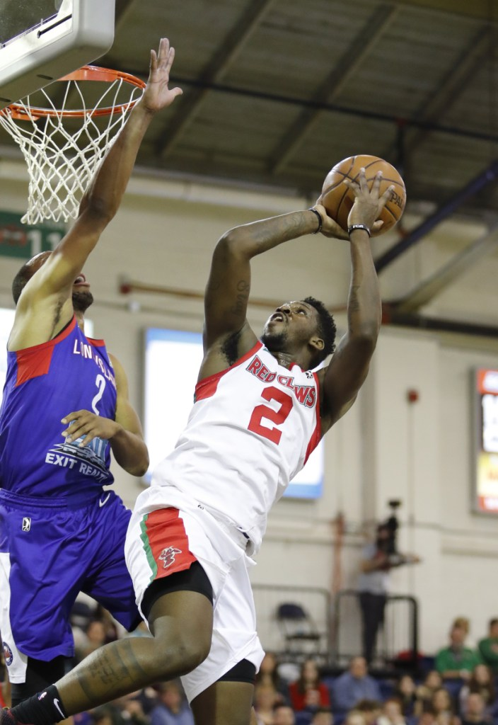Maine's L.J. Peak shoots over Long Island's Akil Mitchell in the first quarter the Red Claws' 109-100 win Sunday at the Portland Expos.