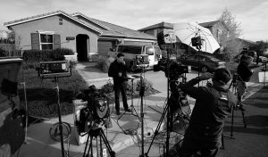 MEMBERS OF THE MEDIA work outside a home on Tuesday where police arrested a couple on Sunday accused of holding 13 children captive in Perris, California.