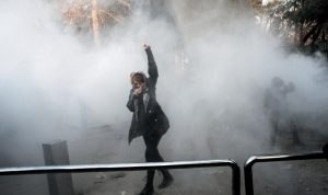 A UNIVERSITY STUDENT attends a protest inside Tehran University while a smoke grenade is thrown by anti-riot Iranian police, in Tehran, Ira, in this Saturday file photo taken by an individual not employed by the Associated Press and obtained by the AP outside Iran. Iran has seen its largest anti-government protests since the disputed presidential election in 2009, with thousands taking to the streets in several cities in recent days. Travel restrictions and moves by the government to shut down social media networks have limited the ability of journalists to cover the ongoing unrest, which Iranian state television said has killed 12 people.