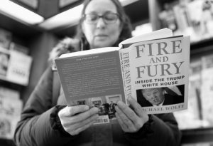 """KATHY MALLIN, from Glenview, Ill., looks over a copy of the book """"Fire and Fury: Inside the Trump White House"""" by Michael Wolff at Barbara's Books Store, Friday, Jan. 5, in Chicago."""