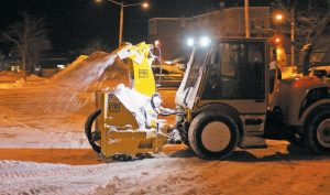 A SNOW THROWER clears the sidewalk along Bank Street in Brunswick before dawn this morning.