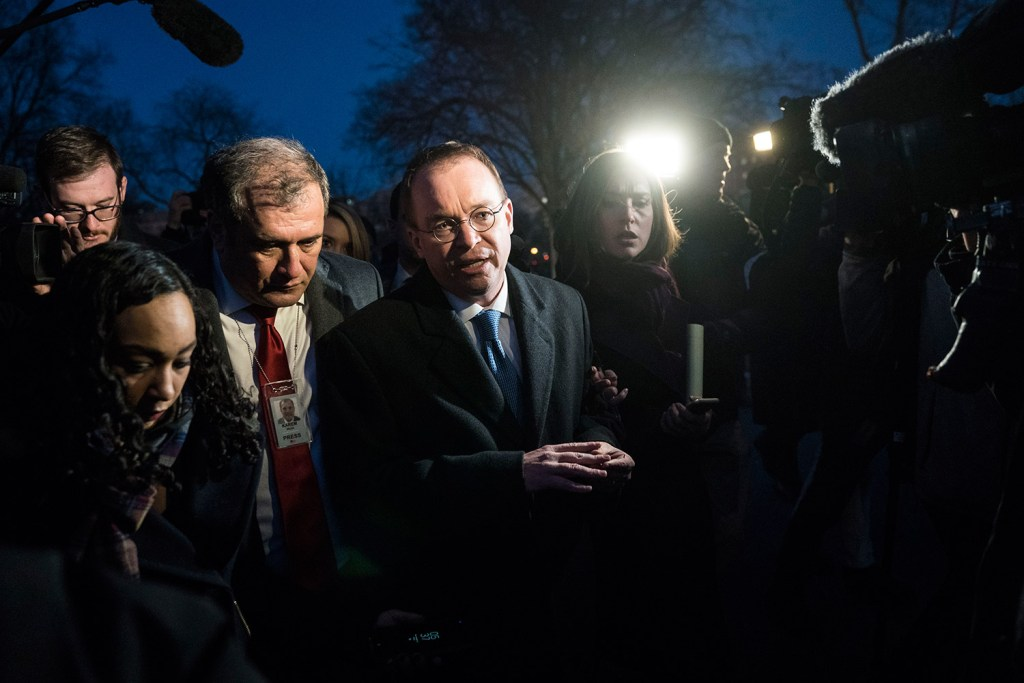 Members of the media swarm Office of Management and Budget Director Mick Mulvaney at the White House on Friday night as he talks about a possible government shutdown.