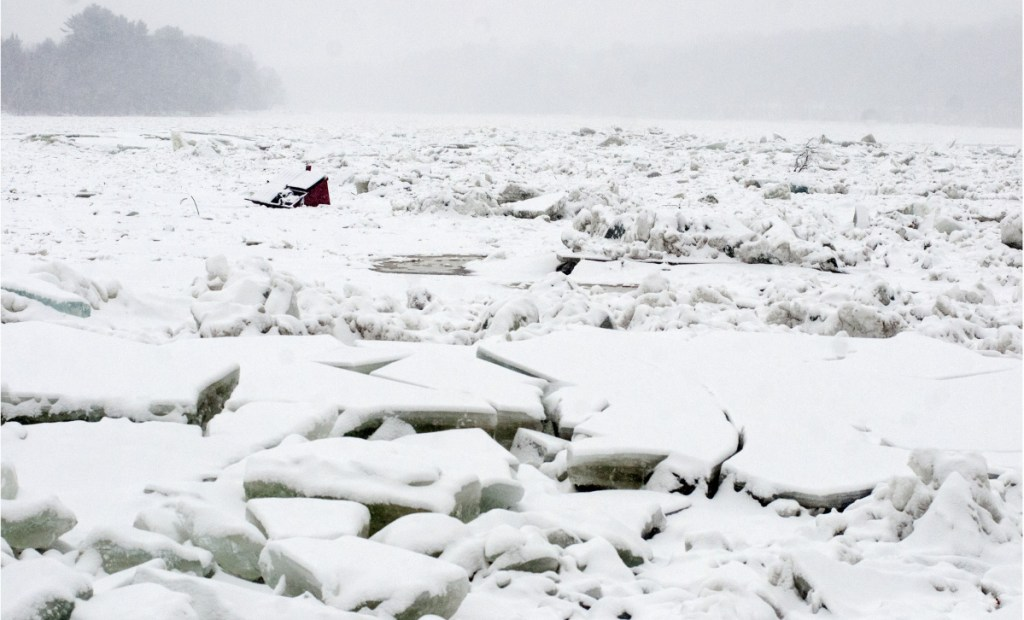 A dumpster that floated away on the Kennebec River during a Jan. 14 flood lies stuck in the ice in Hallowell.