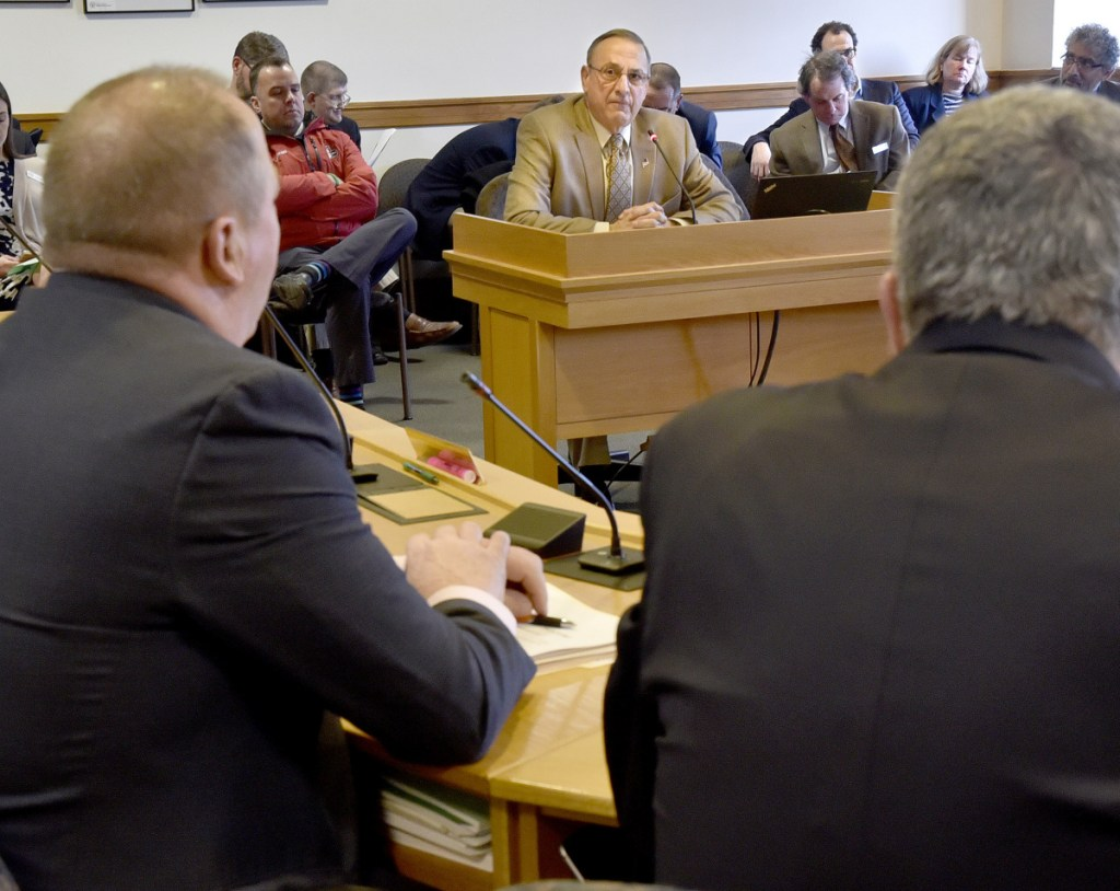 """Gov. Paul LePage listens Tuesday during an appearance before the Joint Standing Committee on Taxation in support of L.D. 1629, a bill titled """"An Act to Protect the Elderly from Tax Lien Foreclosures,"""" at the State House in Augusta."""
