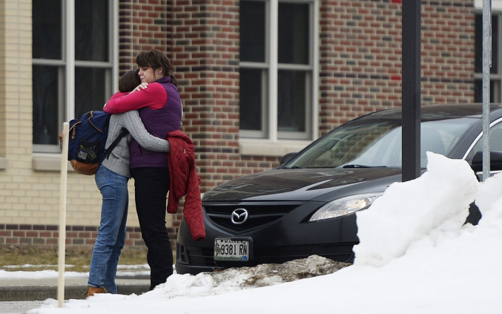 """Robin Davis hugs her daughter Caroline, a sophomore, as she picks her up Thursday at South Portland High School. Earlier in the day, a 15-year-old student on his way to school was arrested on a charge of terrorizing after allegedly posting a social media message about """"shooting up the school."""""""