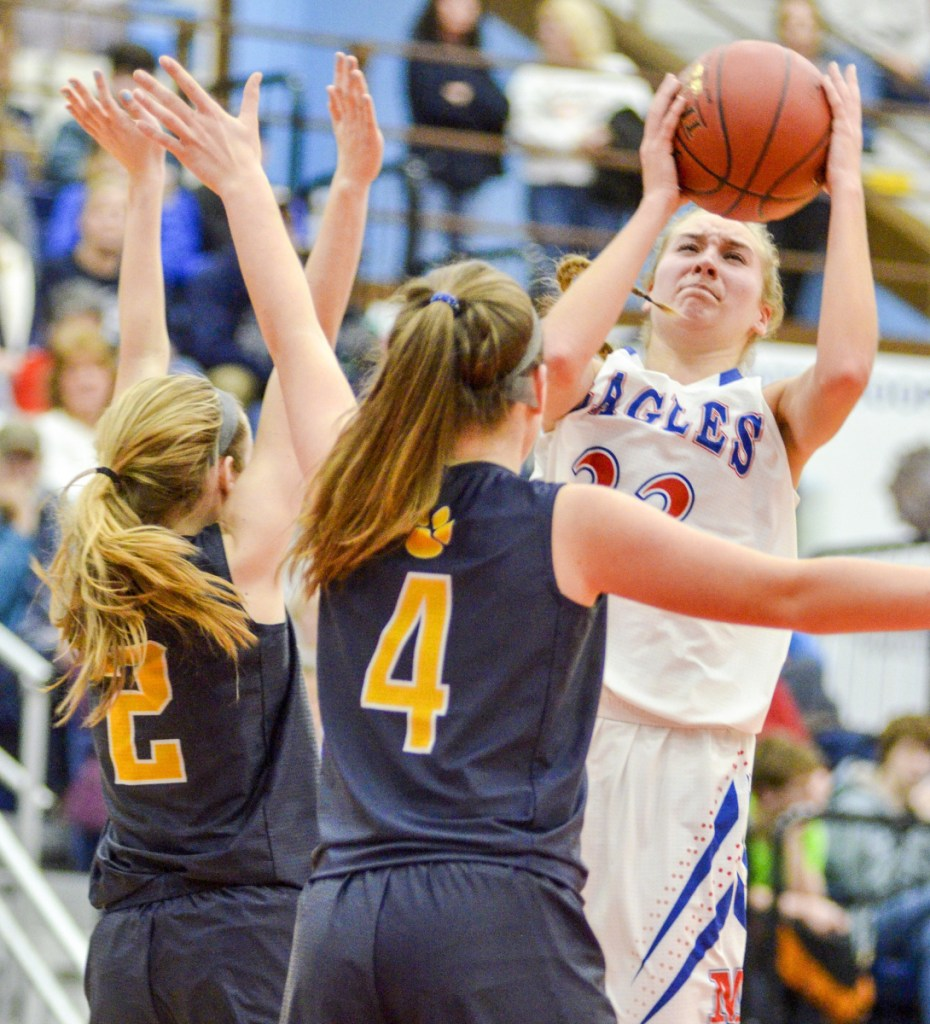 Ally Turner of Messalonskee, right, looks for room while guarded by Cheyenne Nash, left, and Aubrey Schaeffer of Medomak Valley during Messalonskee's 63-49 victory Friday in a Class A North quarterfinal at the Augusta Civic Center.