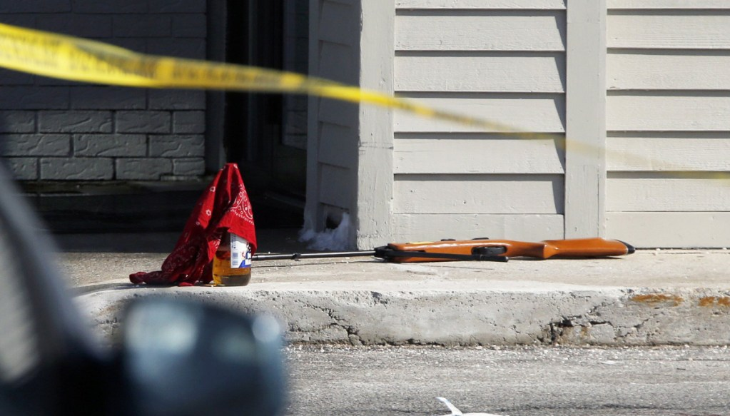 A pellet rifle and a bandanna-covered bottle of malt liquor remain at the strip mall in Portland after Chance Baker, 22, was shot by police last year.