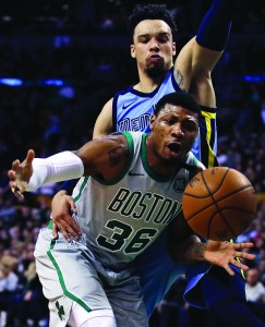 Boston Celtics guard Marcus Smart (36) is fouled by Memphis Grizzlies forward Dillon Brooks, top, on a drive to the basket during the first quarter of an NBA basketball game in Boston, Monday. AP NEWSWIRE