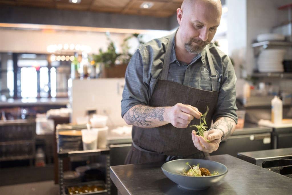 "Chef Josh Berry garnishes toasted chickpea falafel with roast cauliflower at Union. The dish is vegetarian and gluten-free. ""We experimented,"" Berry says of creating dishes while he's tried on various dietary restrictions. ""There were a lot of epic failures, but some things worked out well."""