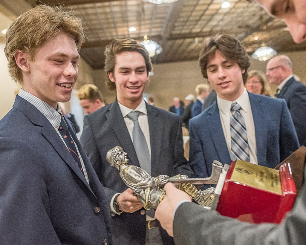 Theo Hembre, left, shows off the Travis Roy Award to Falmouth teammates Marcus Cady and Louis Mainella after the awards banquet Sunday at the Ramada Inn in Lewiston.