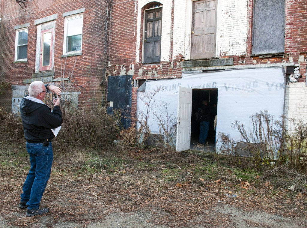 Randall Behm, of Army Corps of Engineers, takes a photo last November of the back walls of 149-167 Water St. in downtown Gardiner as part of an effort to develop strategies to reduce the risk of floods.