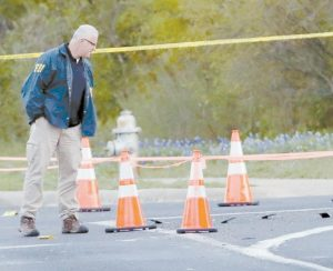 OFFICIALS WORK near the site of Sunday's explosion, Monday, in Austin, Texas.