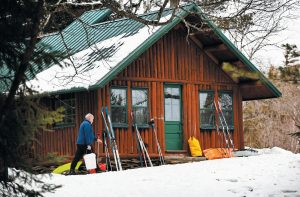 SKIER DAN CASSIDY hauls a bucket of snow to melt for drinking water at the Haskell Hut in the Katahdin Woods and Waters National Monument in northern Maine earlier this month. Overnight lodging in the wood stove-heated cabin is free for backcountry enthusiasts.