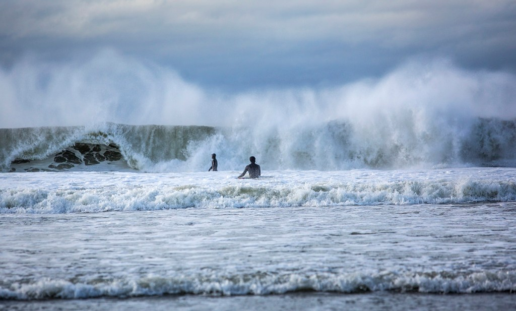 Surfers wade into heavy surf while making their way out to a break at Higgins Beach on March 5 in Scarborough.