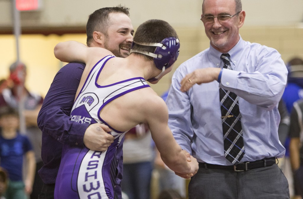 Marshwood's 126-pound wrestler Liam Coomey celebrates a victory over Noble's Sam Martel with coaches Pat Howard and Matt Rix (right) during the Class A state wrestling championship in Sanford on February 17.