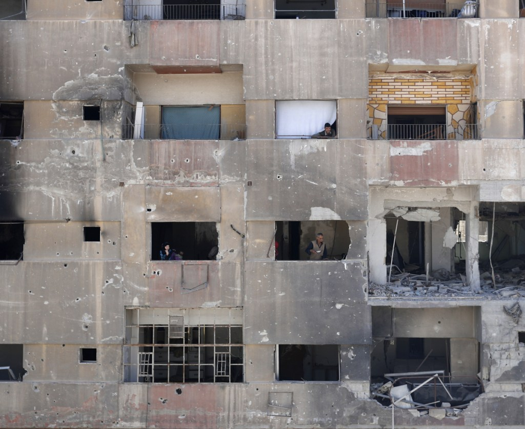 Residents look out of their damaged apartment building on Monday near where the alleged chemical weapons attack took place in the town of Douma, Syria.