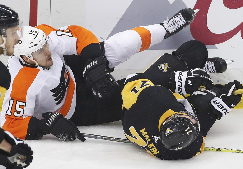 Pittsburgh's Evgeni Malkin and Philadelphia's Jori Lehtera collide and slide into the boards during the first period Friday night in Pittsburgh. The Flyers won 4-2, but still trail the series 3-2.