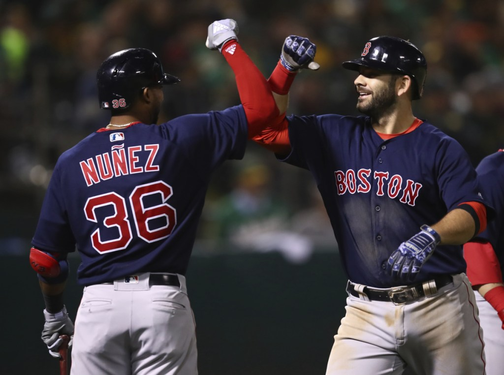 Boston's Mitch Moreland, right, celebrates with Eduardo Nunez after hitting a grand slam in the sixth inning at Oakland on Friday night. (AP Photo/Ben Margot)
