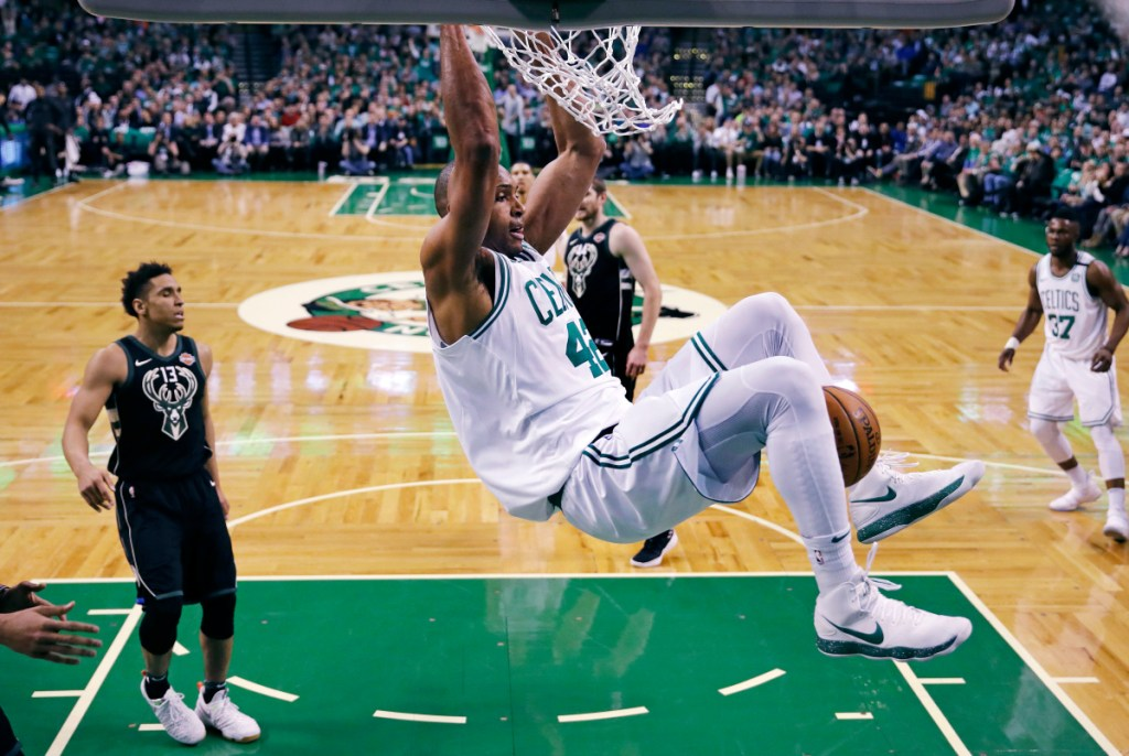 Boston Celtics forward Al Horford hangs from the rim after dunking against the Milwaukee Bucks during the first quarter of Game 5 of an NBA basketball first-round playoff series in Boston, Tuesday, April 24, 2018. (