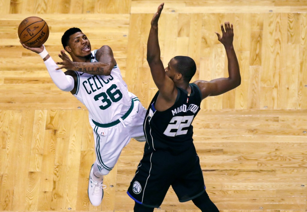 Boston guard Marcus Smart (36) is fouled by Milwaukee forward Khris Middleton (22) on a drive to the basket during the second half of Game 5 of a first-round playoff series Tuesday in Boston.
