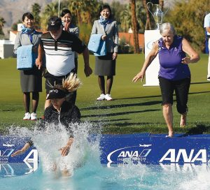 PERNILLA LINDBERG, bottom left, jumps into the pond with her father Jan Lindberg, left, and mother, Gunilla Lindberg, right, after defeating Inbee Park on the 10th hole during the eighth playoff hole of the LPGA Tour ANA Inspiration golf tournament at Mission Hills Country Club in Rancho Mirage, Calif., on Monday. THE ASSOCIATED PRESS