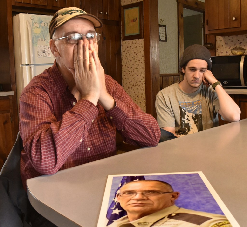 """Tom Cole, left, brother of slain Somerset County Deputy Cpl. Eugene Cole, in the photograph, tries to regain his composure while talking about his brother in Skowhegan on Sunday. At right is his son Scott. """"He was more than a brother and friend,"""" Tom Cole said. """"He was a father figure."""""""