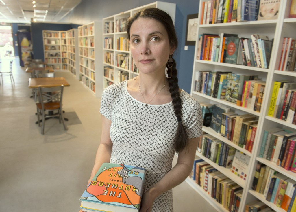 Allison Krzanowski, co-owner of Quill Books and Beverage in Westbrook, pulled books written by Junot Diaz from her shelves recently.