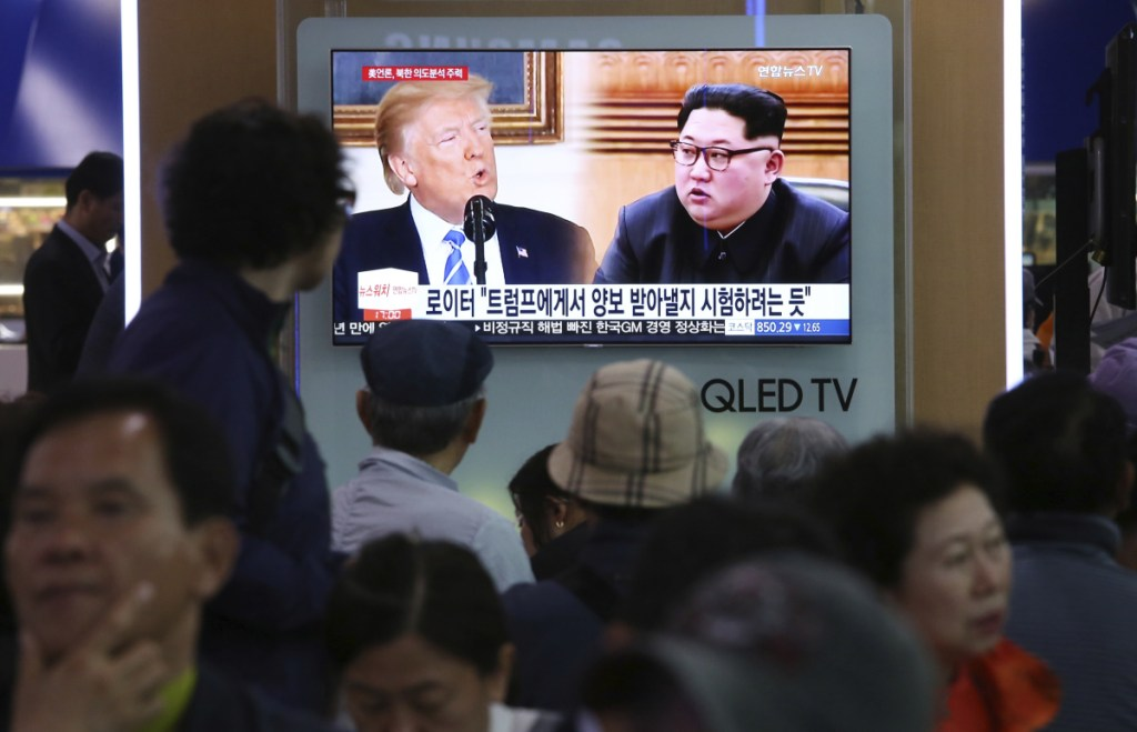 """People watch a TV showing split-screen images of U.S. President Trump and North Korean leader Kim Jong Un during a news program at the Seoul Railway Station in Seoul, South Korea, on Wednesday. North Korea on Wednesday threatened to scrap a historic summit next month between Kim and Trump, saying it has no interest in a """"one-sided"""" affair meant to pressure Pyongyang to abandon its nuclear weapons. The signs read: """" Trying to test Trump."""""""