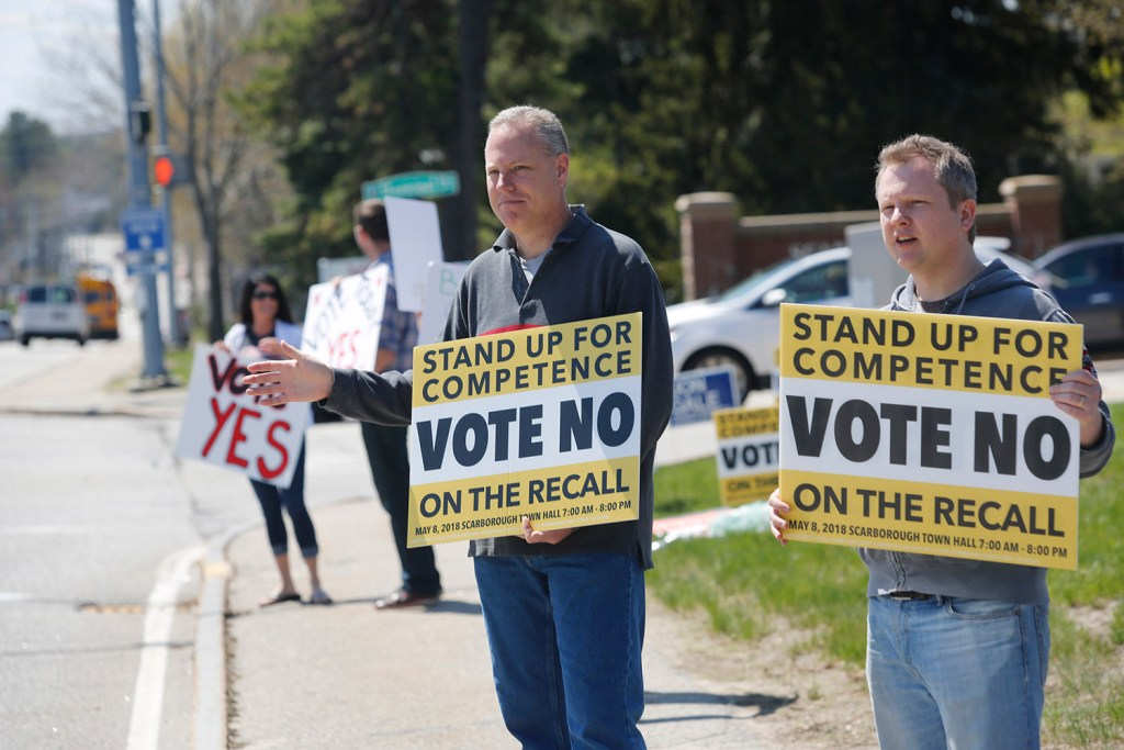 """Rodger Kueck, left, and Brent Crossman hold up """"No"""" signs to passing traffic on Route 1 as Racquel Undlin and Matt Sither hold """"Yes"""" signs. The special election on the recall of three school board members clearly divided the town."""