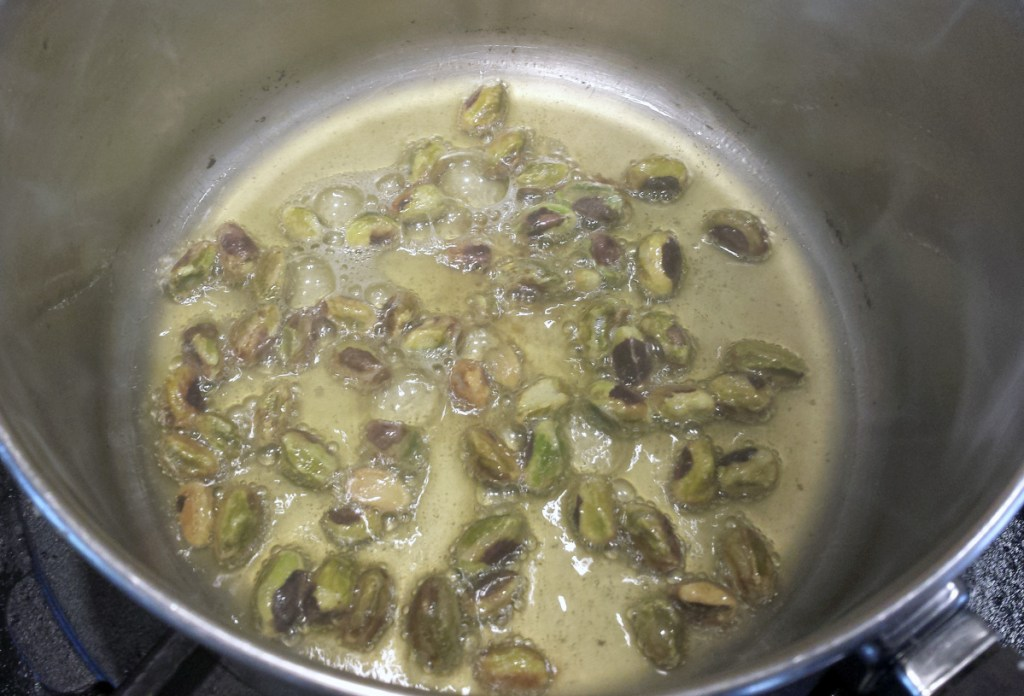 Raw pistachios brown in clarified butter.