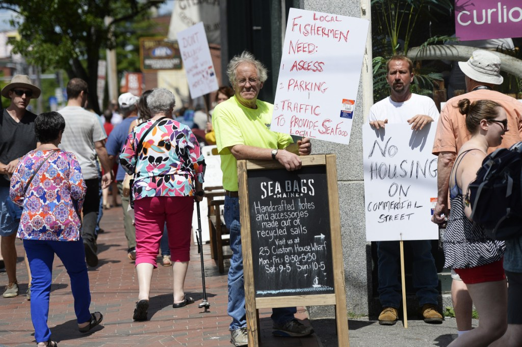 Local fisherman Willis Spear, center, and Timothy Allen hold signs in protest of another hotel on the Portland waterfront Saturday.