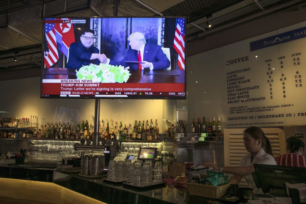 A screen displays a news broadcast of President Trump and North Korean leader Kim Jong Un shaking hands at a document-signing event, in a restaurant in Singapore on Tuesday.