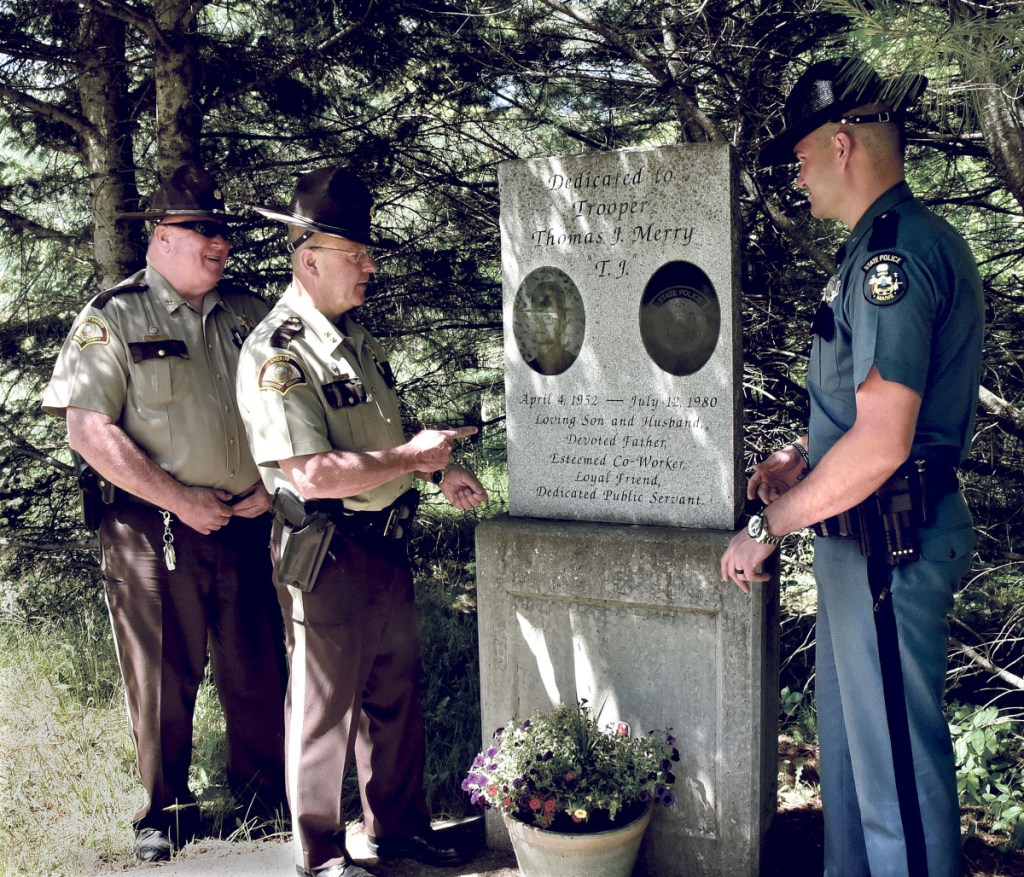 The site of the memorial to Trooper Thomas Merry, who died in the line of duty in 1980, has become obscured along the woods line on Route 2 in Palmyra. Somerset County Deputy and vice-chair of the Palmyra Board of Selectmen Mike Cray, left, Somerset County Sheriff Dale Lancaster and Trooper Eric Bronson on Thursday discuss an effort to relocate the memorial to another site nearby.